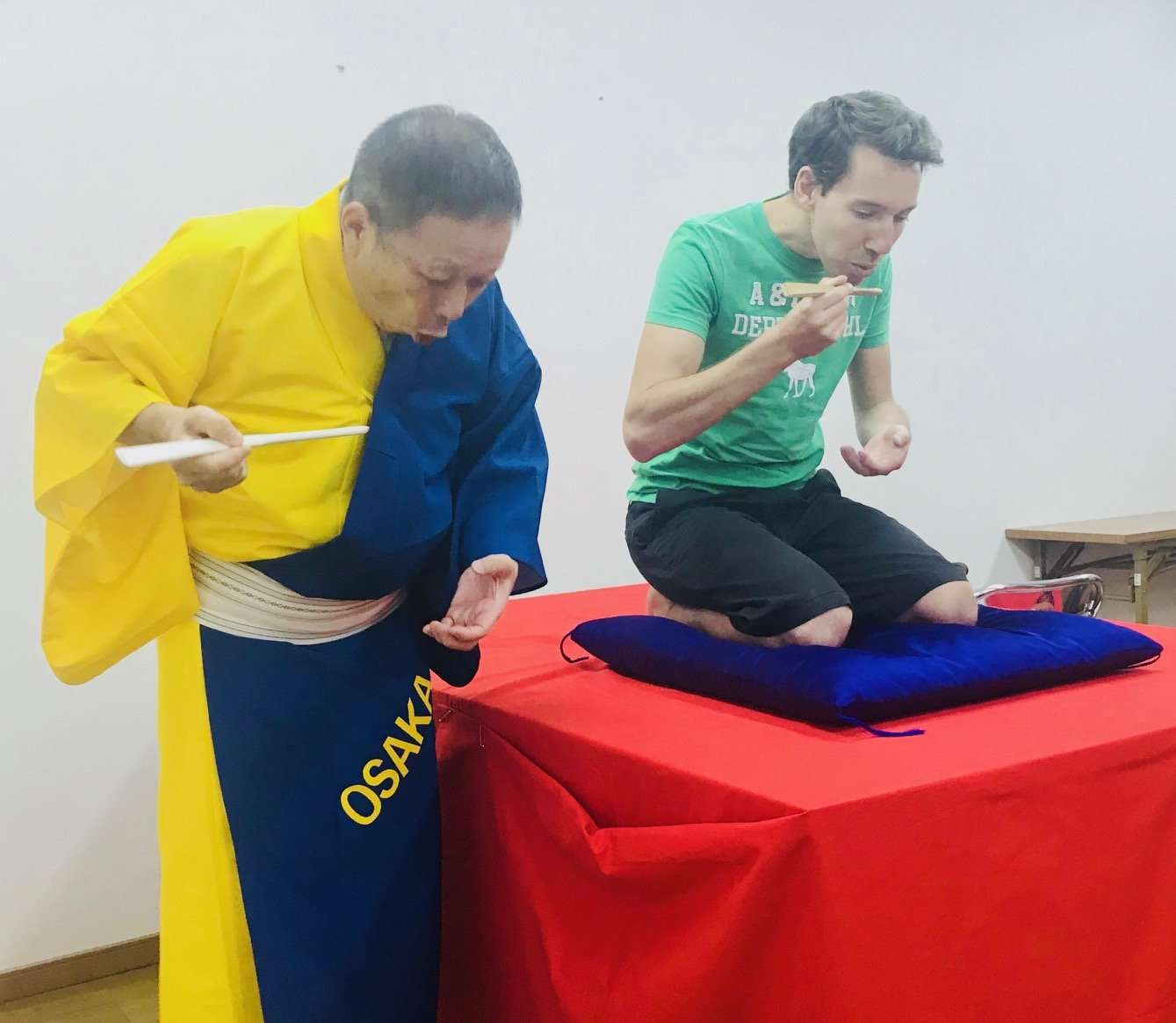 Showto teaches a workshop on Rakugo and how to eat noodles pantomiming with only a fan.